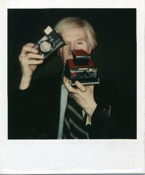 Andy Warhol with two cameras at the Factory.