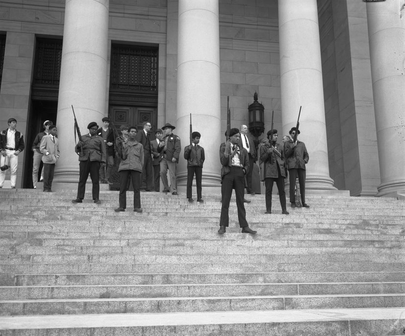 "UNKNOWN PHOTOGRAPHER, OLYMPIA, WA, FEBRUARY 1969. Washington State Archives. Armed members of the Seattle chapter of the Black Panther Party standing on the state capitol steps protesting a proposed law limiting the ability to carry firearms in a ""manner manifesting an intent to intimidate others."""