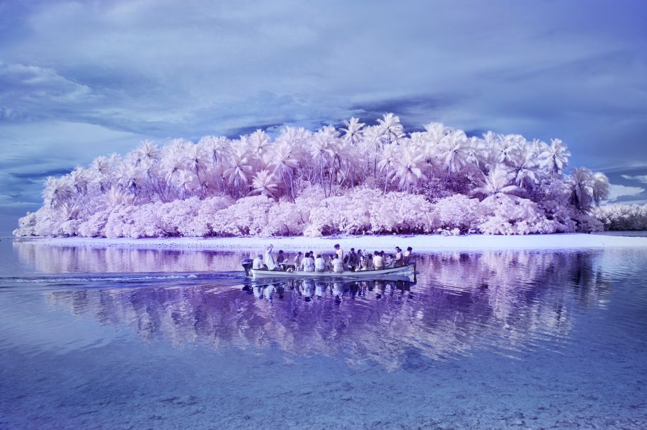 6. On the way back from a picknick to one of the uninhabited small islands around Pingelap with the colorblind Pingelapese and all the children of the one school of the island. The bay is now protected, islanders are no longer allowed to fish for turtles. Because of the infrared colors the scene looks very romantic, at the same time there's the visual connotation of the boats full of refugees setting off for a better future. The Island of the Colorblind.In the late eighteenth century a catastrophic typhoon swept over Pingelap, a tiny atoll in the Pacific Ocean. One of the survivors, the king, carried the rare achromatopsia-gen that causes complete colorblindness. The king went on to have many children and as time passed by, the hereditary condition affected the isolated community and most islanders started seeing the world in black and white.Achromatopsia is characterized by extreme light sensitivity, poor vision, and complete inability to distinguish colors. Portraying the islanders that by their fellow Micronesians are described as 'blind' resulted in a conceptual selection of images that mask their eyes, their face, or their 'vision' and at the same time invite the viewer to enter a dreamful world of colorful possibilities.