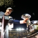 Manning eagerly grabs the Vince Lombardi Trophy!