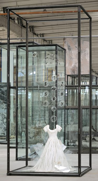 Anselm Kiefer Die Schechina, 2010. Painted resin dress, glass shards, steel, numbered glass discs, and wire in inscribed glass and steel vitrine. 179 x 82.5 x 82.5 inches (455 x 210 x 210 cm) Hall Collection. Courtesy Hall Art Foundation Photography: Charles Duprat © Anselm Kiefer