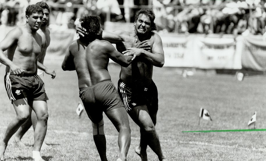 CANADA - JULY 31: Krazy about kabaddi. Thousands gather at Varsity Stadium for kabaddi tournament yesterday as a member of Scotland's team; below left; battles a member of the B.C. team. Six teams are competing in the ancient Indian sport for the Kabaddi Canada Cup. (Photo by Rick Eglinton/Toronto Star via Getty Images)
