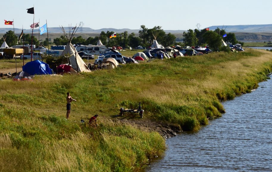 A view of a protest encampment near Cannon Ball, North Dakota where members of some 200 Native American tribes from across the US and Canada have gathered to lend their support to the Standing Rock Sioux Tribe's opposition to the Dakota Access Pipeline (DAPL, September 3, 2016. Drive on a state highway along the Missouri River, amid the rolling hills and wide prairies of North Dakota, and you'll come across a makeshift camp of Native Americans -- united by a common cause. Members of some 200 tribes have gathered here, many raising tribal flags that flap in the unforgiving wind. Some have been here since April, their numbers fluctuating between hundreds and thousands, in an unprecedented show of joint resistance to the nearly 1,200 mile-long Dakota Access oil pipeline. / AFP / Robyn BECK (Photo credit should read ROBYN BECK/AFP/Getty Images)