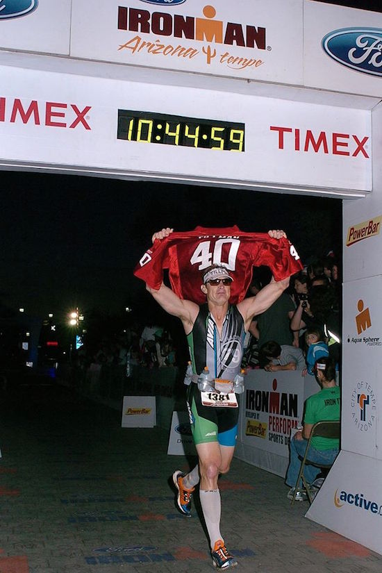 Byrnes hoisting Tillman's jersey across the Ironman finish line in 2011.