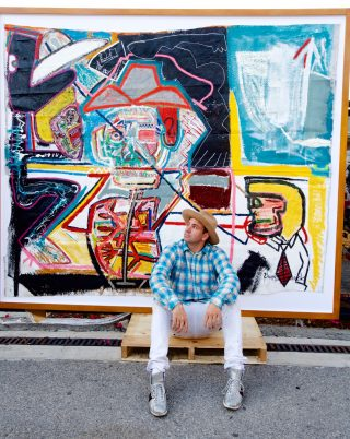 """Photo: Danny Mannick in front of his painting """"The Last Cowboy""""."""